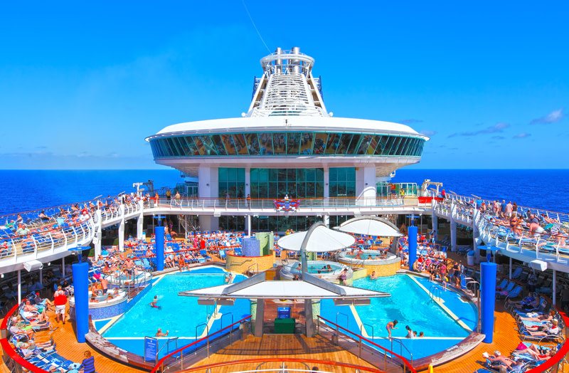 People and children enjoying a cruise ship pool deck under a blue sky.