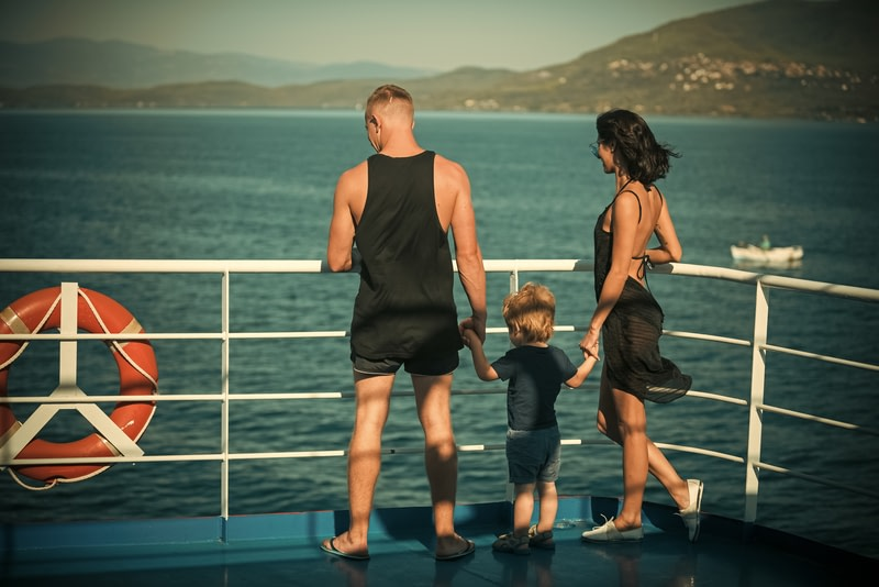 Family travelling on cruise ship on sunny day.